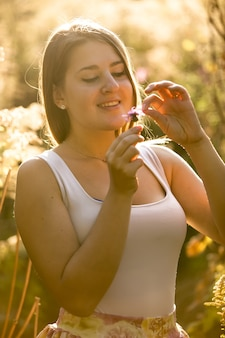 Portrait tonique d'une jeune femme souriante arrachant une fleur au pétale