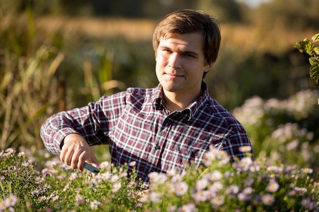 Portrait tonique de jeune homme souriant taille des fleurs au jardin