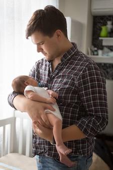 Portrait tonique de jeune père tenant un nouveau-né sur les mains à la maison