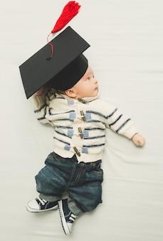 Portrait tonique d'un mignon petit garçon posant dans une casquette de graduation noire