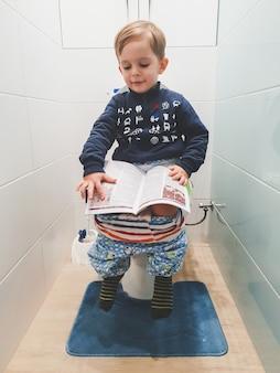 Portrait tonique d'un petit garçon intelligent se tenant sur les toilettes et lisant des magizines