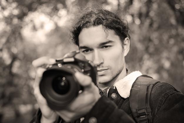 Portrait tonique d'un photographe avec appareil photo pendant la prise de vue en extérieur