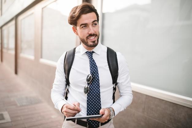 Portrait d'un touriste masculin heureux avec tablette numérique