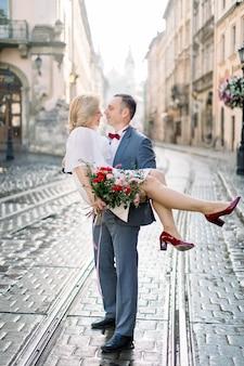 Portrait de toute la longueur d'un beau couple d'âge mûr dans la vieille ville antique. bel homme en costume tient une charmante femme blonde sur les mains. célébration d'anniversaire de mariage