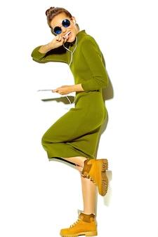Portrait de toute la longueur de la belle femme brune souriante mignonne heureuse dans des vêtements d'été décontractés hipster vert isolé sur blanc, écouter de la musique dans un smartphone avec un casque