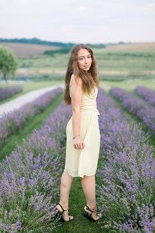 Portrait de toute la longueur de la belle jeune femme dans le champ de lavande. jolie fille aux cheveux longs et sains profitant d'une promenade à l'extérieur dans un champ de lavande en fleurs