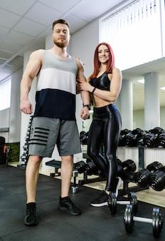 Portrait de toute la longueur d'un bodybuilder mâle et d'une femme musclée dans une salle de sport.