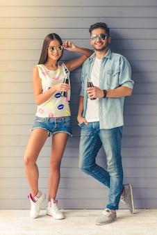 Portrait de toute la longueur d'un couple d'adolescents à lunettes de soleil.