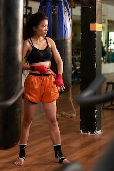 Portrait de toute la longueur du boxeur muay thaï enroulant la bande rouge au poignet avant l'entraînement
