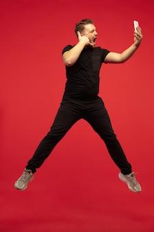 Portrait de toute la longueur du jeune homme sautant en hauteur isolé sur un mur rouge. modèle caucasien masculin. copyspace. émotions humaines, expression faciale, concept sportif.