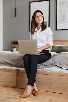 Portrait de toute la longueur d'une femme d'affaires adulte confiante en costume formel tapant sur un ordinateur portable assis sur le lit dans l'appartement