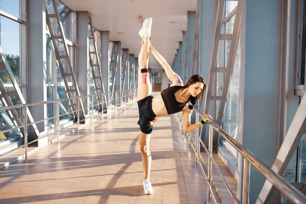 Portrait de toute la longueur d'une femme brune musclée pratiquant la scission. jeune athlète flexible féminine posant avec la jambe vers le haut, tenant la main courante à l'intérieur, bande de kinésiologie colorée sur le corps, intérieur futuriste.