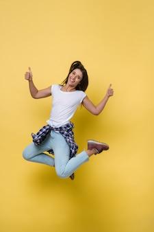 Portrait de toute la longueur d'une femme caucasienne occasionnelle gaie sautant