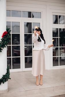 Portrait de toute la longueur d'une femme élégante magnifique avec de longs cheveux noirs dans des perspectives beiges et des talons tenant des lumières du bengale étincelantes dans les deux mains debout à l'extérieur de la maison.