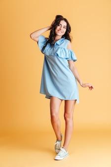 Portrait de toute la longueur d'une femme souriante et joyeuse posant en robe bleue isolée