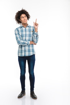 Portrait de toute la longueur d'un homme afro-américain réfléchi et heureux aux cheveux bouclés pointant le doigt vers le fond isolé sur un mur blanc