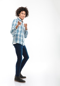 Portrait de toute la longueur d'un homme afro-américain souriant aux cheveux bouclés pointant du doigt isolé sur un mur blanc