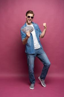 Portrait de toute la longueur d'un homme joyeux en chemise de jeans tenant un tas de billets d'argent en se tenant debout et en célébrant isolé sur fond rose