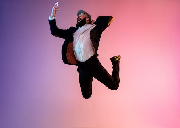 Portrait de toute la longueur d'un homme sautant heureux en néon et fond dégradé