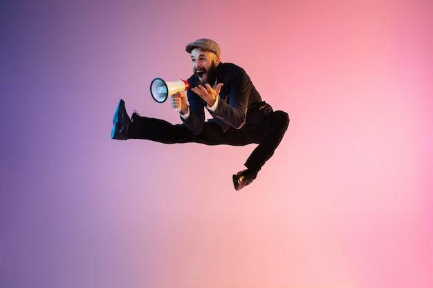 Portrait de toute la longueur d'un homme sautant heureux portant des vêtements de bureau en néon isolé sur fond dégradé. émotions, annonce. utiliser la paix, gagner, vendre, faire du shopping, se dépêcher, travailler au bureau.