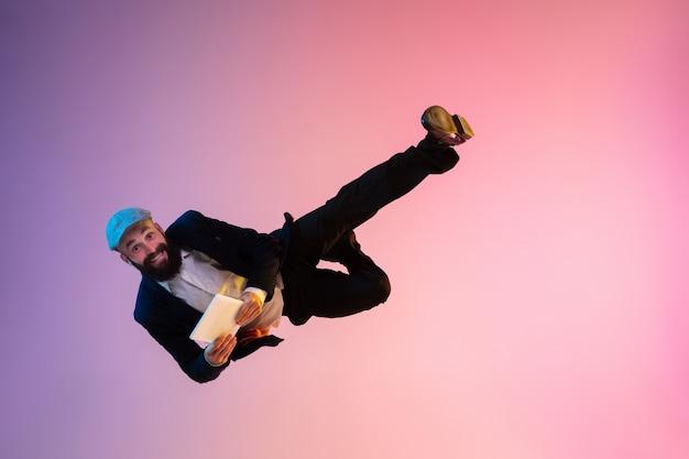 Portrait de toute la longueur d'un homme sautant heureux portant des vêtements de bureau en néon isolé sur fond dégradé. émotions, annonce. utiliser une tablette, gagner un pari ou une vente, faire du shopping, se dépêcher, travailler au bureau.