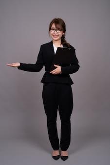 Portrait de toute la longueur de la jeune femme d'affaires asiatique debout