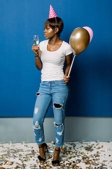 Portrait de toute la longueur d'une jeune femme africaine gaie tenant des tas de ballons à air chaud et champagne isolé sur un espace bleu. fête d'anniversaire, concept de célébration.