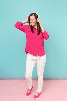 Portrait de toute la longueur d'une jeune femme amusante en chemisier rose, pantalon blanc, casque dansant isolé sur un mur pastel bleu rose vif.