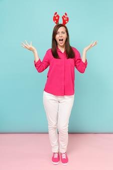 Portrait de toute la longueur d'une jeune femme amusante en chemisier rose, pantalon blanc, cornes de cerf posant isolées sur un mur pastel bleu rose vif.