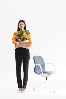 Portrait de toute la longueur d'une jeune femme bouleversée vêtue d'une tenue élégante tenant une boîte avec des fournitures de bureau en raison d'un tir isolé sur un mur blanc