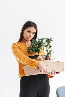 Portrait de toute la longueur d'une jeune femme frustrée vêtue d'une tenue élégante tenant une boîte avec des fournitures de bureau en raison d'un tir isolé sur un mur blanc