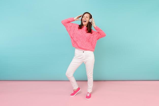 Portrait de toute la longueur d'une jeune femme heureuse en pull rose tricoté, pantalon blanc, casque