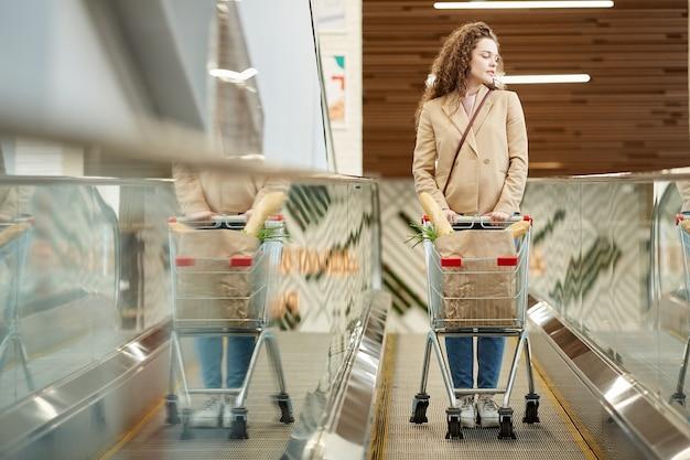 Portrait de toute la longueur de la jeune femme moderne poussant le panier avec des produits d'épicerie en se tenant debout sur l'escalator dans le marché de producteurs