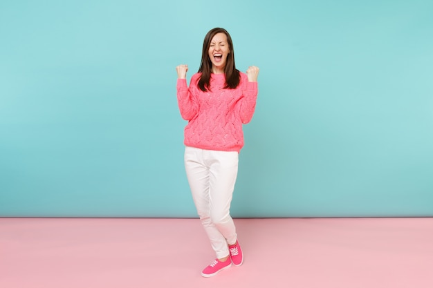 Portrait de toute la longueur d'une jeune femme souriante en pull rose tricoté, pantalon blanc posant