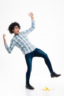 Portrait de toute la longueur d'un jeune homme afro-américain glissant sur une peau de banane isolée sur un mur blanc