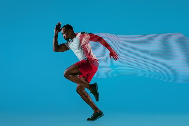 Portrait de toute la longueur d'un jeune homme en cours d'exécution musculaire africain actif isolé