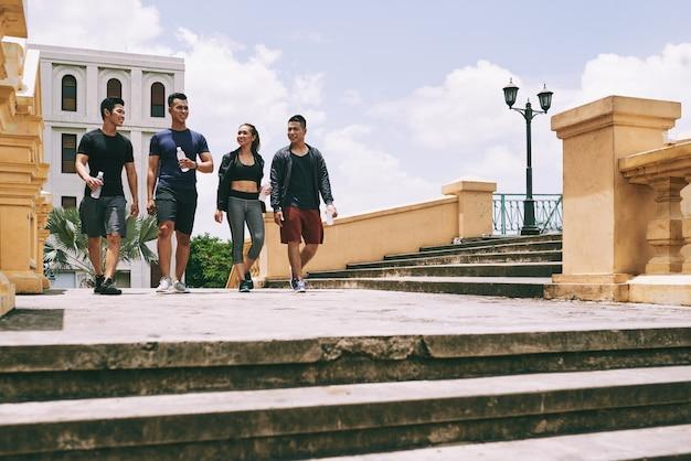 Portrait de toute la longueur de jeunes gens prenant une pause dans un exercice de jogging marchant en plein air