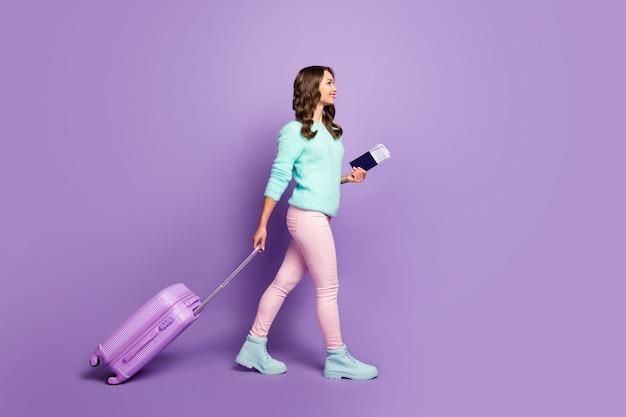 Portrait de toute la longueur de la jolie dame drôle marchant enregistrement de l'aéroport avec des billets valise de voyage à roulettes porter des bottes de pantalon rose pastel pull flou.