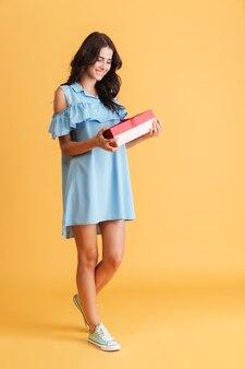 Portrait de toute la longueur d'une jolie femme souriante en robe tenant une boîte-cadeau isolée