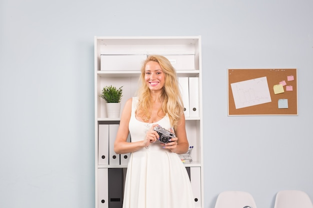 Portrait de toute la longueur d'une jolie fille souriante en robe prenant une photo sur un appareil photo rétro en surface de bureau.