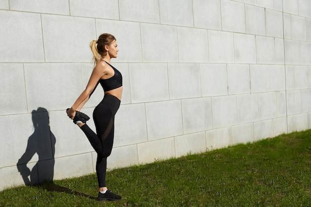 Portrait de toute la longueur de la jolie jeune femme faisant des exercices physiques à l'extérieur sur l'herbe verte le jour d'été ensoleillé, étirement des muscles quadriceps, vêtue d'une tenue noire élégante. sports et bien-être