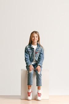 Portrait de toute la longueur de la jolie petite adolescente dans des vêtements de jeans élégants souriant