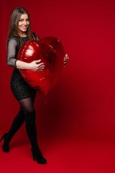 Portrait de toute la longueur de la superbe brune joyeuse en robe noire et bottes hautes marchant avec un gros ballon gonflable en forme de coeur rouge.