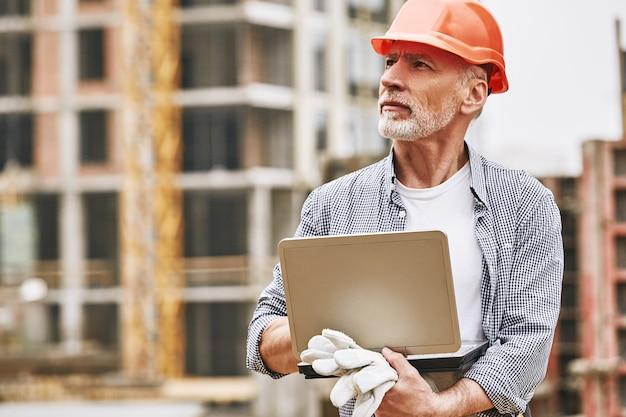 Portrait de travail à l'extérieur d'un ingénieur de construction senior occupé dans des vêtements de protection à l'aide d'un ordinateur portable et