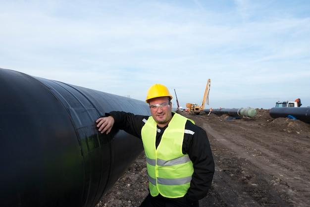 Portrait d'un travailleur de champ pétrolifère debout par tuyau de gaz au chantier de construction