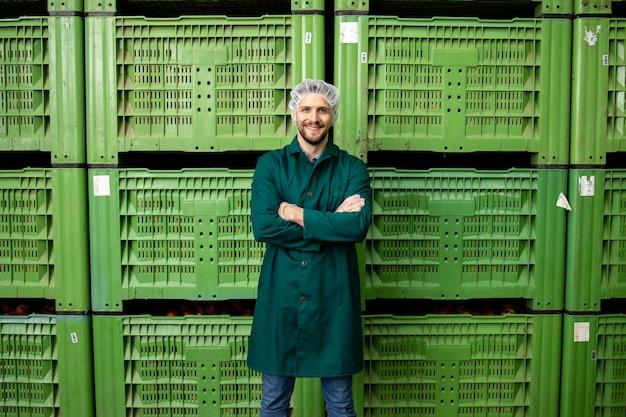 Portrait de travailleur debout par des caisses de fruits de pomme dans l'entrepôt de l'usine d'aliments biologiques.