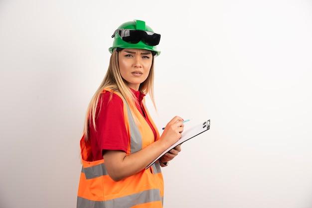 Portrait travailleur femme industrie portant des uniformes de sécurité et des lunettes debout sur fond blanc.