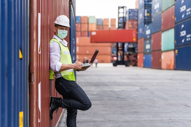 Portrait travailleur homme à l'aide d'un ordinateur portable waring masque chirurgical et tête blanche de sécurité pour se protéger de la pollution et des virus sur le lieu de travail au cours de l'inquiétude concernant la pandémie de covid