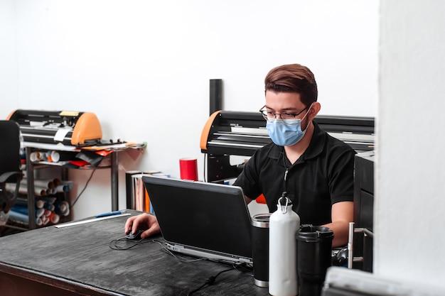 Portrait d'un travailleur masculin latino-américain sur un ordinateur portable portant un masque facial. nouveau concept normal.