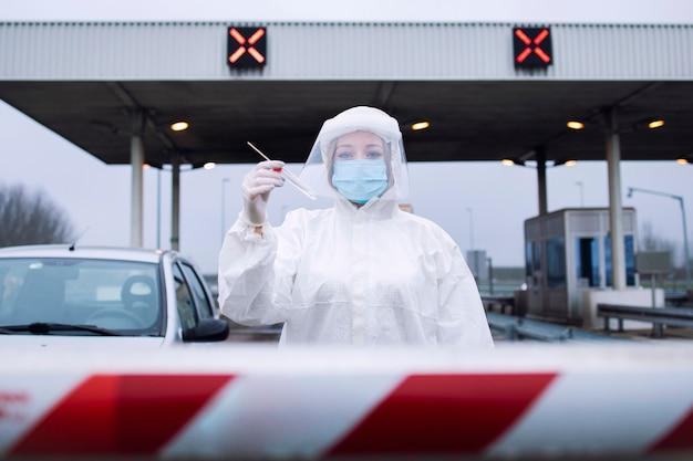 Portrait de travailleur médical de la santé en costume blanc de protection debout au point de contrôle du passage de la frontière pour préformer le test pcr sur les passagers en raison de la pandémie du virus corona.